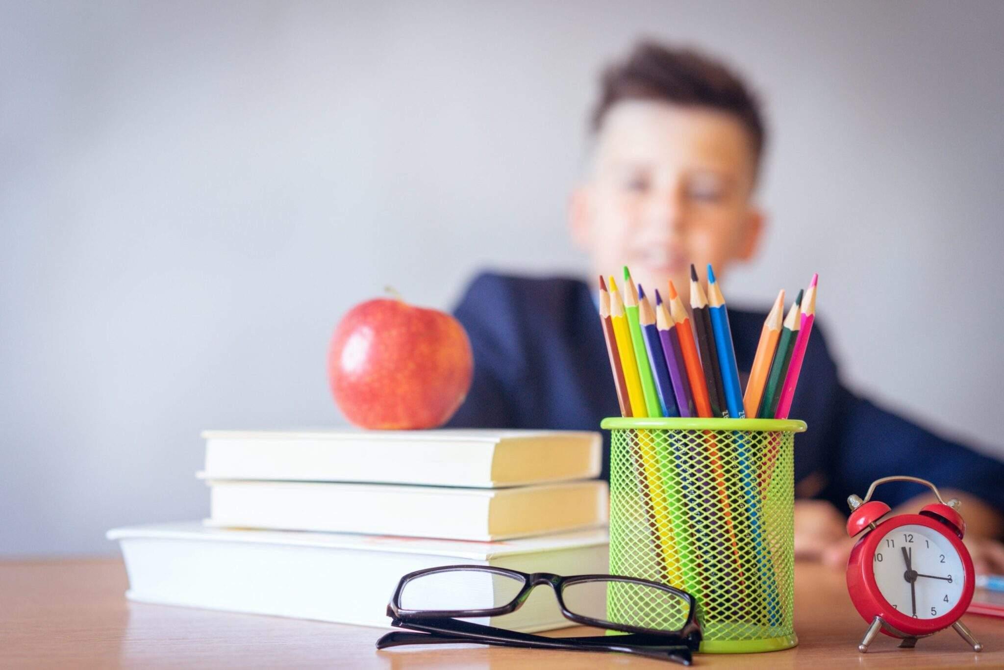 Jeune élève avec livres et stylos