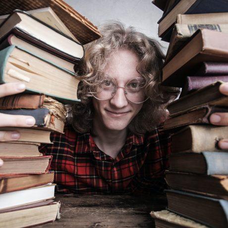 Jeune homme avec piles de livres
